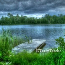 Stormy Skies overhead at the lake with a pier in the foreground, by © Terry Tasche